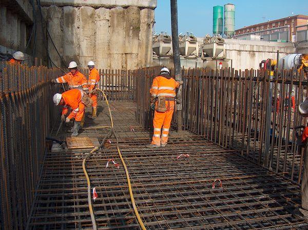 Liberata la prima parte di terreno è stato possibile realizzare la mega trave a C di coronamento delle «pareti» ancora annegate all'interno del terreno in modo da irrigidire l'intero camerone. Sono state impiegate notevoli quantità di acciaio ad alte prestazioni.