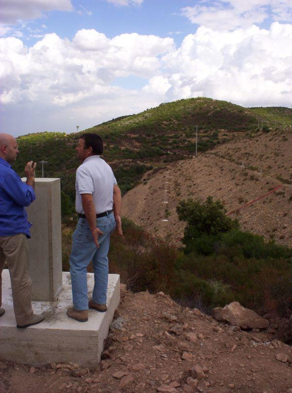 Fase di realizzazione dei capisaldi di triangolazione e collimazione: sono evidenti i getti dei plinti sulle bancate del paramento di valle.