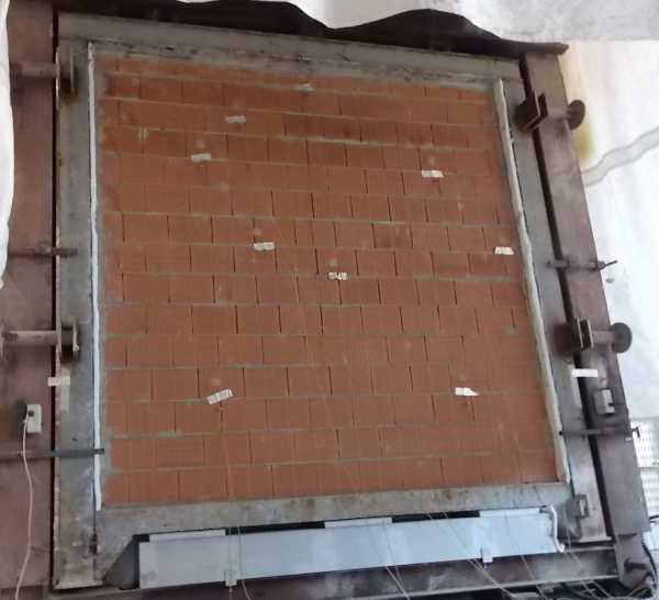 Figura 5. Prova di resistenza al fuoco su parete in laterizio portante: si notano i martinetti posti nella parte inferiore del telaio per l'applicazione del carico.